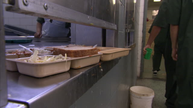 vídeos de stock, filmes e b-roll de prison inmates return trays to the kitchen after a meal. - prisoner
