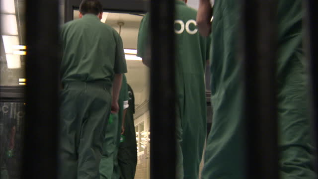prison inmates walk single file through a doorway. - prisoner stock videos & royalty-free footage