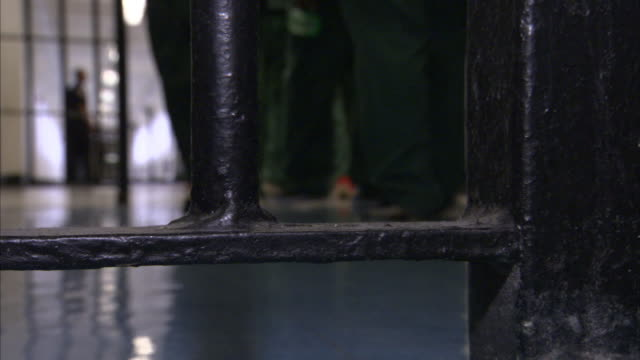 vídeos de stock, filmes e b-roll de prison inmates walk through a security gate. - prisoner