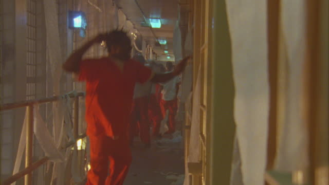 Prison inmates wave and cheer as toilet paper ignites and falls around them.