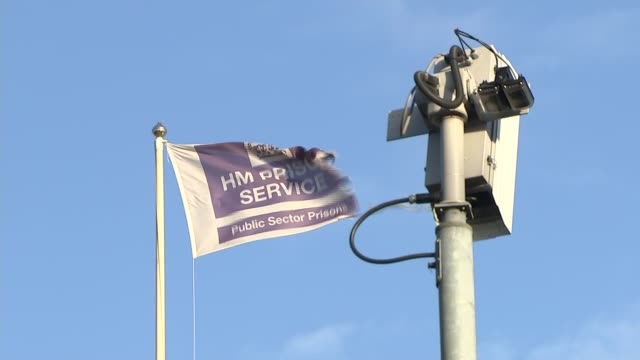 prison service branded 'in crisis' following recent riots and escapes england london prison service flag flying next to broken cctv security camera... - gefängnisausbruch stock-videos und b-roll-filmmaterial