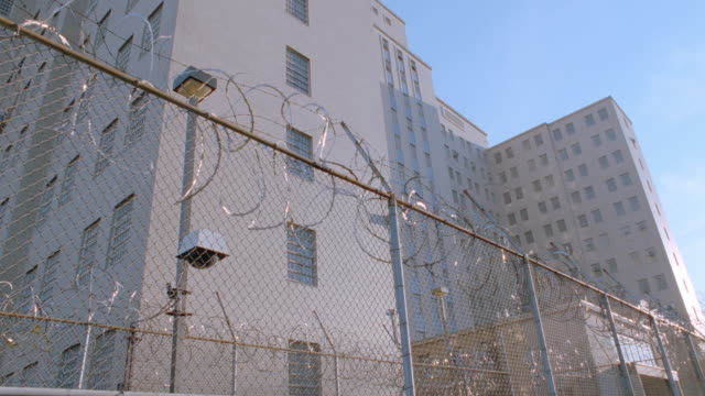 a prison stands behind a fence and razor wire. - fence stock videos & royalty-free footage