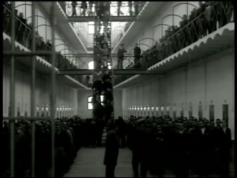 vídeos de stock e filmes b-roll de prison w/ inmates gathering on main floor walking down staircase vs prisoners walking. priest performing catholic mass at alter prison gates bg... - padre