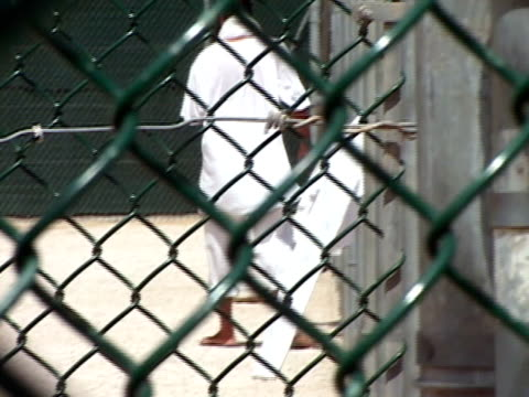prisoner at camp delta 4 walking in fenced prison yard cages at guantanamo bay detention center/ guantanamo province, cuba - guantanamo bay stock videos & royalty-free footage