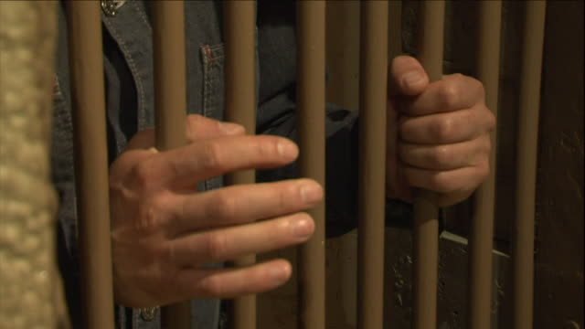 a prisoner grips the bars of his cell. - prisoner hands stock videos & royalty-free footage