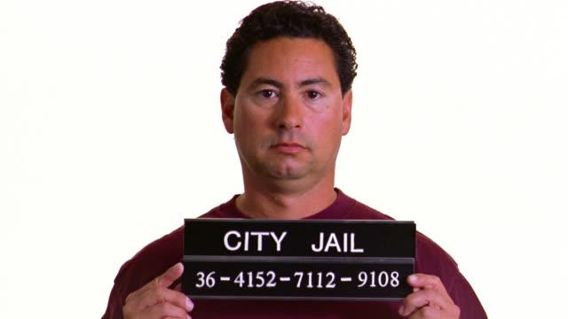 a prisoner holds up his city jail sign as he gets his mug shot taken. - mug shot stock videos & royalty-free footage