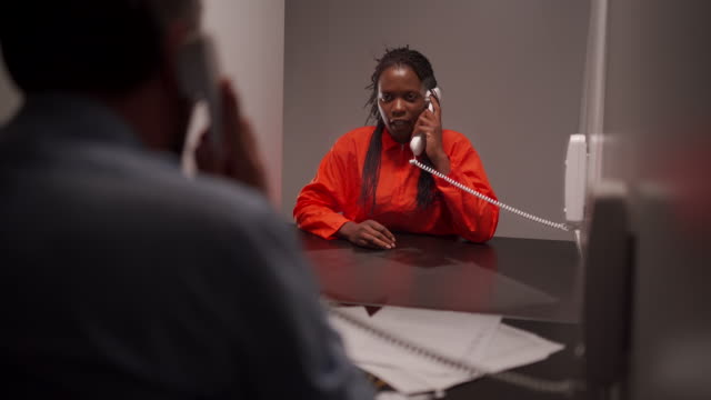 prisoner in jumpsuit talking with prosecutor in visit room at prison - prosecutor stock videos & royalty-free footage