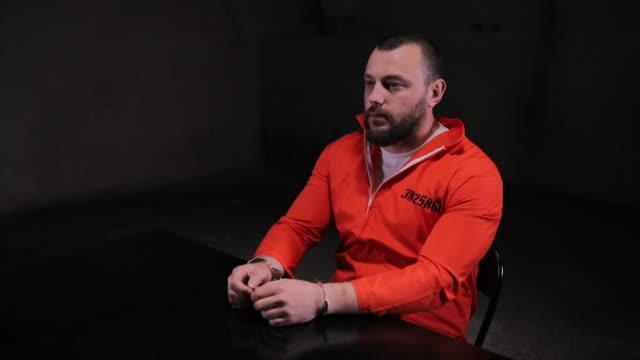 prisoner in orange jumpsuit sitting alone in interrogation room - prisoner orange stock videos & royalty-free footage
