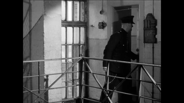 montage prisoner moves in to a cell at a cell block / uk / guard walks new prisoner up stairs to a cell / prisoner walks in cell / guard locks door / prisoner removes embroidery from duffle bag / prisoner tacks embroidery to cell wall - cell membrane stock videos & royalty-free footage