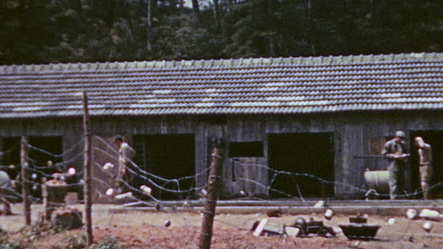 prisoner of war stockade an old barracks surrounded by barbed wire and prisoners standing near the fence / okinawa japan - prisoner of war stock videos & royalty-free footage