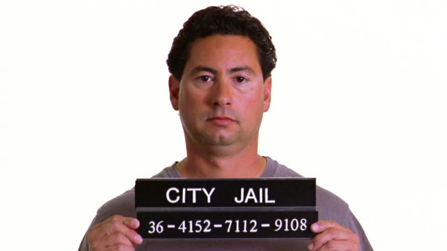 a prisoner poses for a mug shot with a city jail sign. - mug shot stock videos & royalty-free footage
