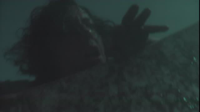 a prisoner reaches over a wall in an attempt to escape. - gefängnisausbruch stock-videos und b-roll-filmmaterial