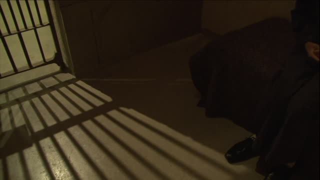 a prisoner sits up on his bed as a guard enters the cell and follows the prisoner out the door. - prisoner stock videos & royalty-free footage