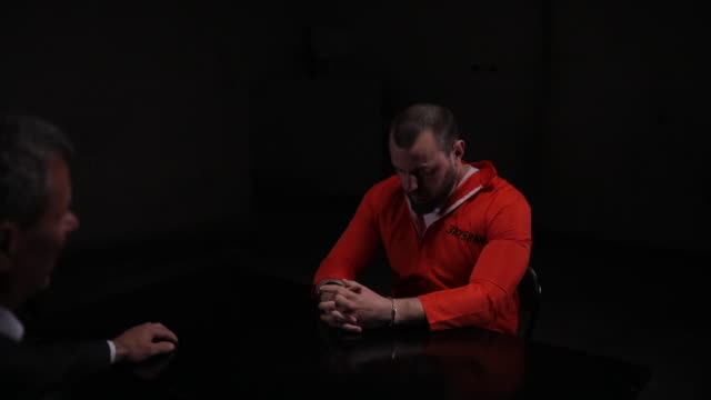 Prisoner sitting in interrogation room with detective