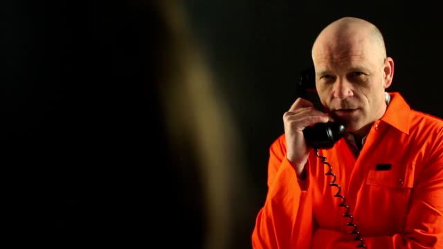 vídeos y material grabado en eventos de stock de preso habla con visitante en el teléfono a través de la plataforma de fibra de vidrio - visita