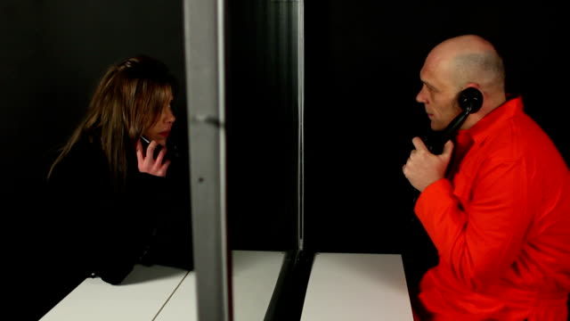 Prisoner talks to visitor on phone through glass