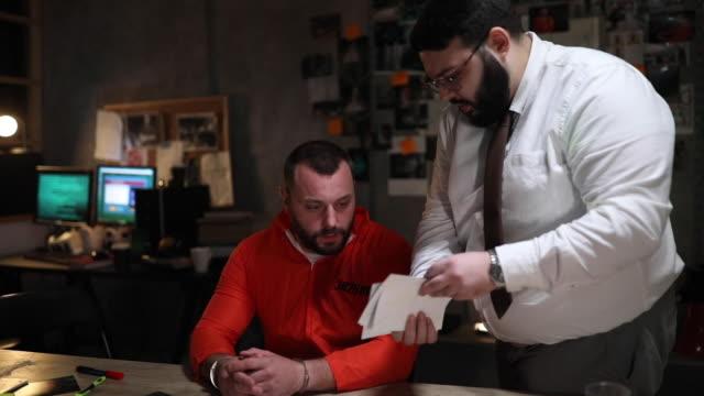 prisoner with handcuffs being interviewed in interrogation room - prisoner orange stock videos & royalty-free footage