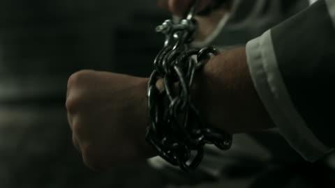 vídeos de stock, filmes e b-roll de prisioneiro com as mãos nas cadeias em cela de prisão - atado