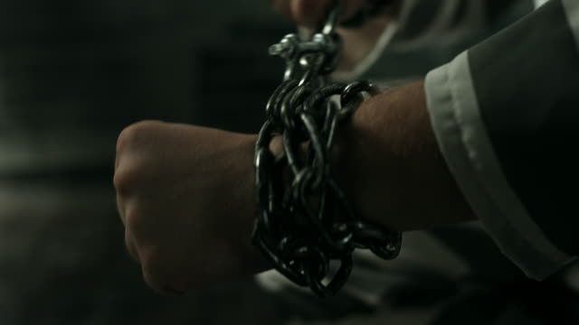 vídeos de stock e filmes b-roll de prisoner with his hands in chains at prison cell - preso