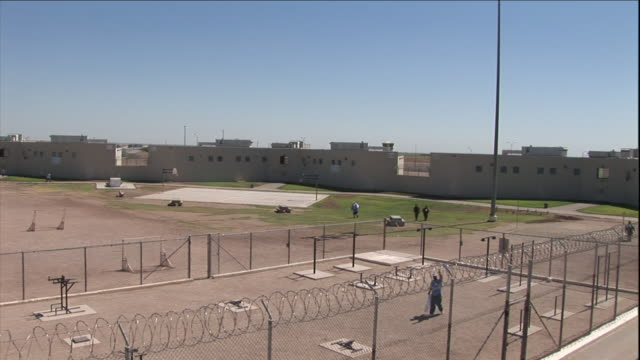 prisoners approach a basketball court in a prison yard. - federal prison building stock videos & royalty-free footage