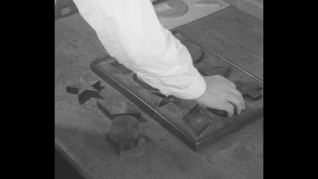 prisoner's arm as he places wooden pieces forming a human figure / arm placing shaped pieces in appropriate spaces on board / note: exact year not... - human arm stock videos & royalty-free footage