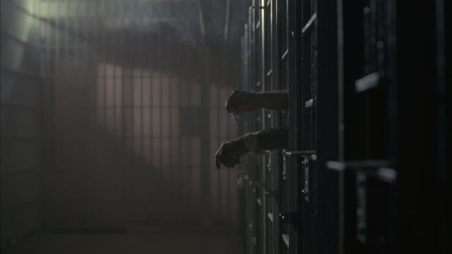 vídeos de stock, filmes e b-roll de a prisoner's arms and smoke from his cigarette fill the dark, gloomy hallway of a south african prison. - prisoner
