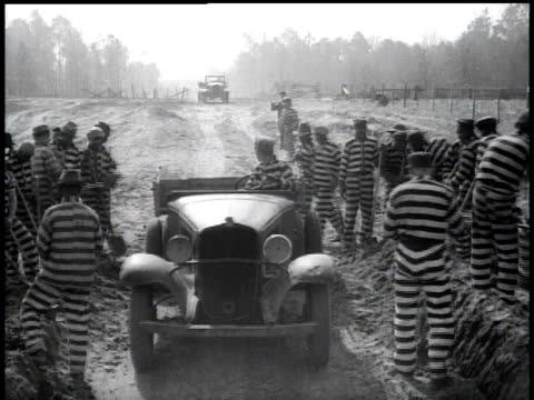 1938 ws prisoners at work shoveling into vehicle / georgia, usa - 鎖点の映像素材/bロール