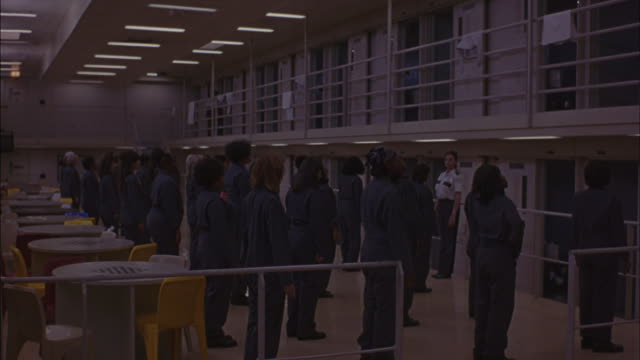 Prisoners exercise in a prison cafeteria courtyard.