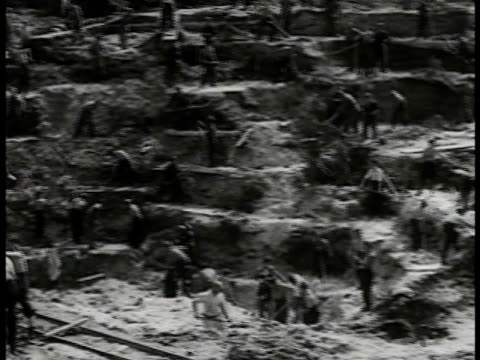prisoners hammering digging on hill side. prisoners digging in entrance of tunnel german guard. vs assembly line of men passing bucket of debris down... - 掘る点の映像素材/bロール