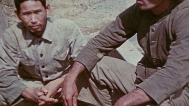 prisoners in pow camp sitting on the ground wearing civilian clothing depressed / okinawa japan - prisoner of war stock videos & royalty-free footage