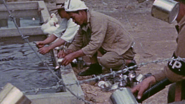 prisoners in pow camp washing empty tin cans by the pond to hang with others on a barbed wire fence with an mp standing guard and ducks watching them... - prisoner of war stock videos & royalty-free footage