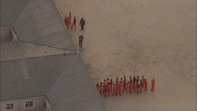 AERIAL ZO Prisoners in yard filing into cells with guards at Pollsmor Prison, Cape Town, Western Cape, South Africa