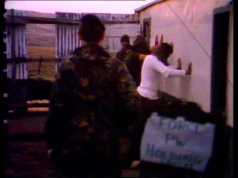 vídeos de stock e filmes b-roll de goose green bv marine standing pow spreadeagled by wall ms 2 leaning against wall ekta lib 14secs tx'd 16682/nat archive tape 20072 2217 to 2230 - ilhas malvinas