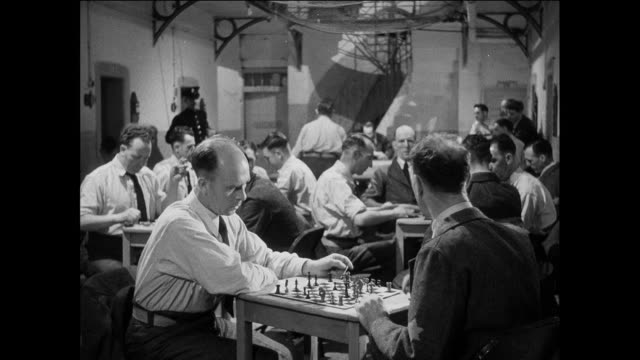 ws prisoners leave prison day room at evening / uk / prisoners play chess at table / guard walks in / guard makes announcement / prisoners put away chess pieces / prisoners walk away - chess stock videos & royalty-free footage