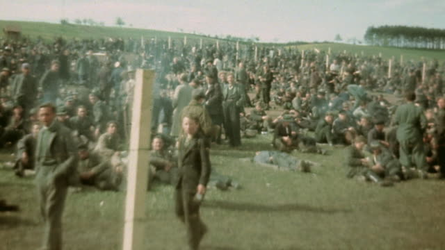 vidéos et rushes de prisoners of war behind barbed wire fencing cooking living waving lifting their hats / germany - 1945