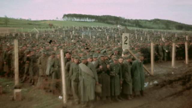 vidéos et rushes de pan prisoners of war behind barbed wire fencing / germany - 1945
