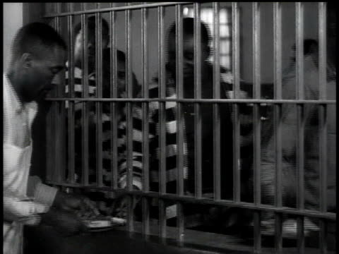 1938 ms prisoners picking up food from behind bars / georgia, usa - uniform stock-videos und b-roll-filmmaterial