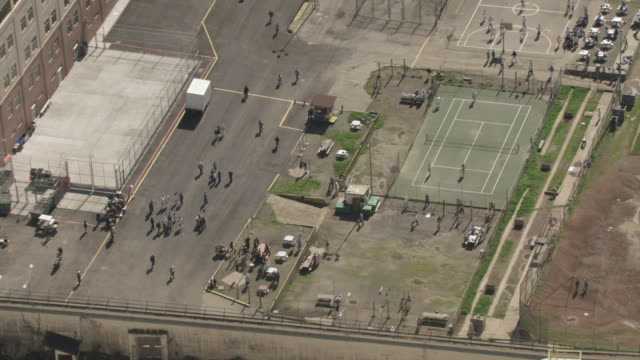AERIAL Prisoners playing basketball and exercising in the state prison yard, and walking across the courtyard between the prison blocks / San Quentin, California, United States