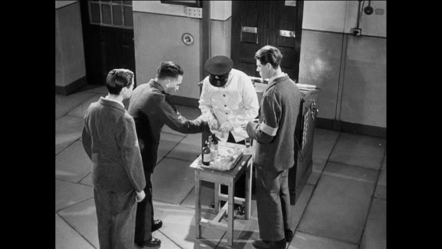 WS prisoners receive medicines from orderly / UK / Prisoner walks to table / prisoner swallows medicine / prisoner walks away / orderly pours medicine in cup