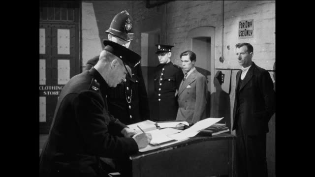 ws prisoners report to guard at desk in prison / uk / police officer and prisoner stand at desk / guard writes and prisoner moves back / guard hands document to officer / officer walks off / guard brings prisoner to desk / prisoner moves back to wall - prisoner education stock videos & royalty-free footage