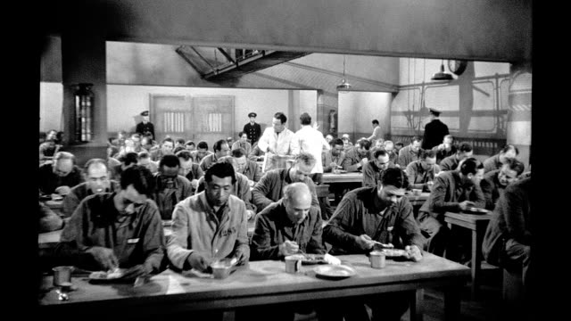 vídeos de stock, filmes e b-roll de 1939, prisoners seated at long tables eating in dining hall - 1930 1939