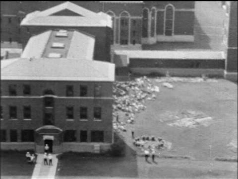 AERIAL prisoners sitting lying on ground at Attica State Prison after riot / NY