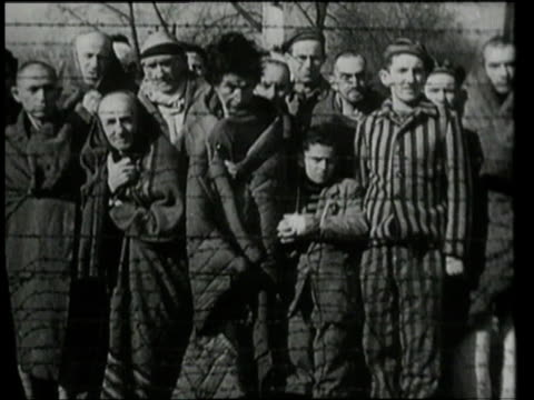 prisoners standing at barbed wire fence, looking out / oswiecim, germany - 1945 stock-videos und b-roll-filmmaterial