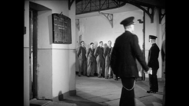 WS prisoners wait in line to report to an office / UK / Prisoners walk in single file / prisoner leaves office / guard steps out from office and calls next in line / prisoner walks to office door