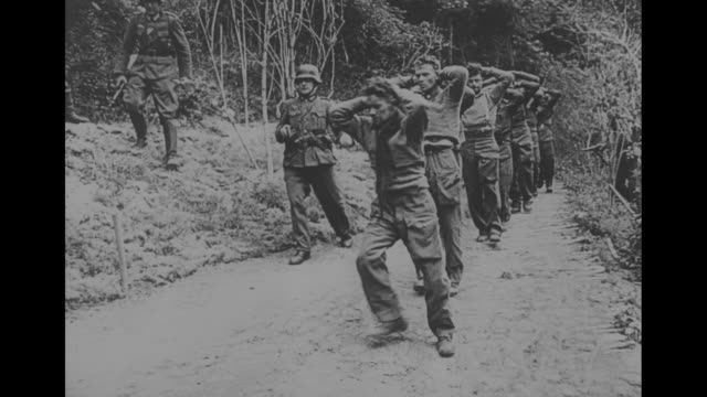 MS prisoners walk down hill with hands in air / MS camouflaged prisoners march / Nazis march Canadian prisoners with hands on heads / VS prisoners...