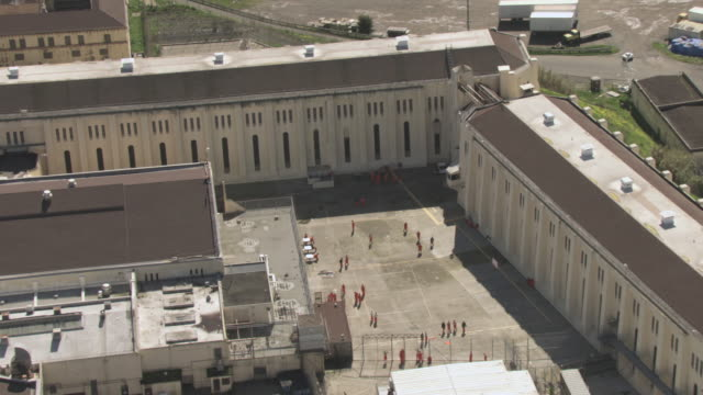 AERIAL Prisoners walking across the courtyard between the prison blocks / San Quentin, California, United States