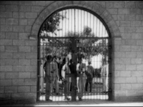 prisoners walking through gate, egyptian political & criminal prisoners walking w/ shakles on legs, sentry guard w/ rifle patrolling top of wall, men... - fucile video stock e b–roll