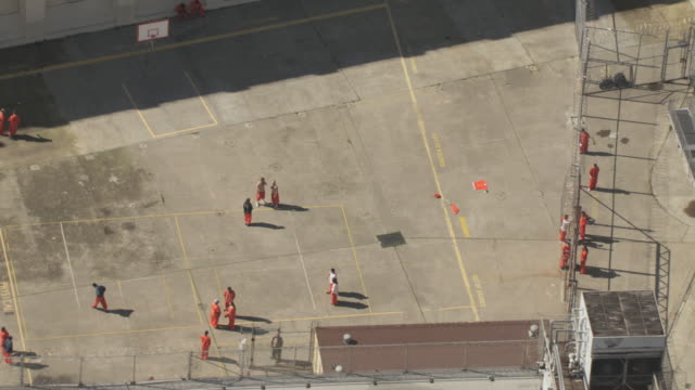 AERIAL Prisoners wearing orange jumpsuits in the courtyard between the prison blocks and standing at the chain link fence / San Quentin, California, United States
