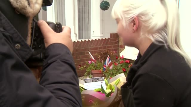 London EXT Woman leaves flowers outside Priti Patel's house as press take photos / Union Jack doormat