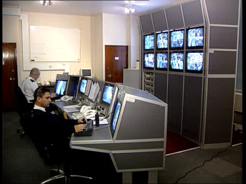 London Man sitting in control room monitoring output from CCTV security cameras Hands on camera controls SIDE Security men sat at controls monitoring...